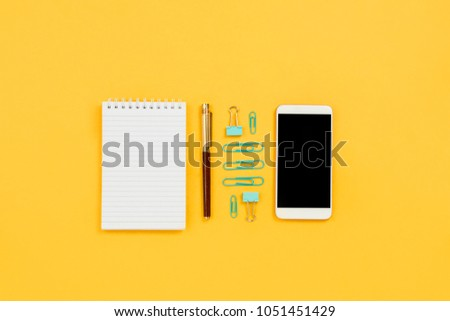 Various business and stationary accessories knolled on yellow - Shutterstock ID 1051451429