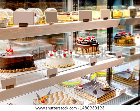 Various Cake with Icing in Refrigerated Bakery Case Cabinet. Chocolate and Cherry Tart Topping on Fridge Display at Culinary Center. Selective Focus