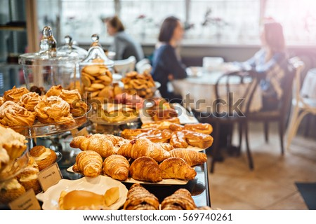 Various cakes on counter of cafeteria with blurred background: customer at restaurant blur background with bokeh.