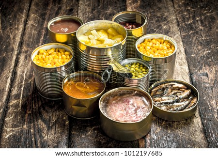 Various canned vegetables, meat, fish and fruits in tin cans. On a wooden background. Stockfoto ©