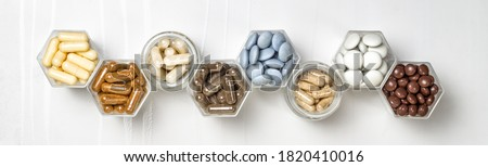 Various capsules and pills with dietary supplements or medicines in hexagonal jars are in the form of a honeycomb Stock photo ©