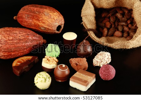 Various chocolate truffles, cocoa pods and cocoa beans in a sack.