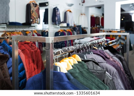 Various coats and blouses on hangers in clothing shop interior