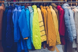Various collection winter coats hanged on a clothes rack.