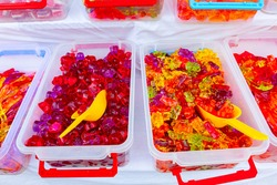 Various colored candies and sweets for sale placed in trays, available at flea market.