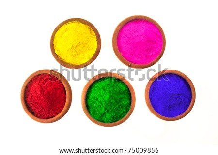 Various colored dyes in earthen bowls isolated on white.