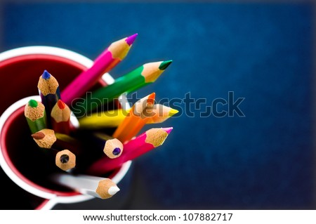 Various Colored Pencils isolated on blue background. Macro with extremely shallow depth of field
