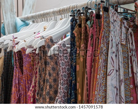 various colorful clothes on a clothes rack for sale