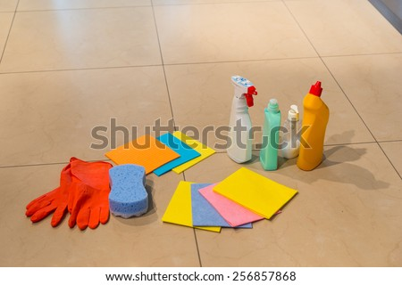 Various colorful household cleaning supplies displayed on a floor with rubber gloves, clothes, a sponge and spray bottles and containers, with copyspace