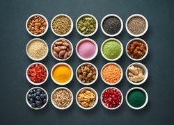 Various colorful superfoods as acai powder, turmeric, matcha green tea, spirulina, quinoa, pumpkin seeds, blueberry, dried goji berries, cape gooseberries, raw cocoa, hemp seeds  on dark background