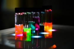 Various colourful analytical sample in glass vial in an inorganic chemistry laboratory experiment on the UV light by a woman scientist