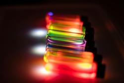 Various colourful reagents in glass vials on UV light in a chemistry laboratory for health care experiment for drug development