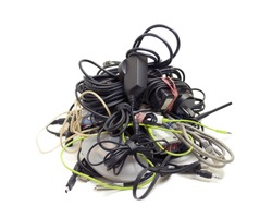 Various computer and electronics cables gathered together into a messy heap, isolated on white.