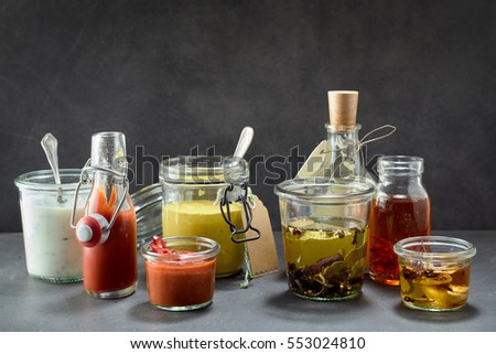 Shutterstock Various condiments in jars and bottles on dark surface with copy space above for concept about food
