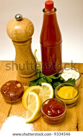 Various condiments including salt, pepper, ketchup, salsa, mustard, lemon, mayonnaise and hot sauce.