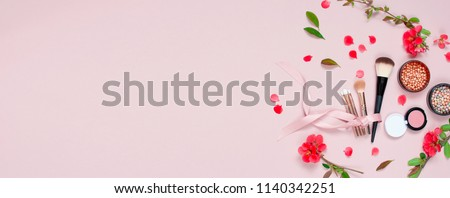 Various cosmetic products for make-up with red flowers on a pink background with copy space. Makeup Accessories Top view Flat Lay. Powder Rouge Eyeshadow Corrector Brushes Mascara. Long banner