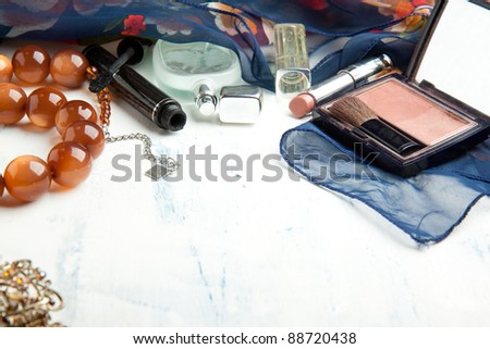 Various cosmetics and beads on white wooden table