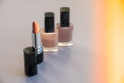 Various Cosmetics isolated on white background. Sun rays. Copy space.Decorative cosmetics.Fashion colors concept.Nude makeup.Selective focus.Nail polish,nail varnish bottles and beige lipstick.