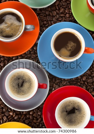 various cups of espresso in colorful cups on spilled coffee beans, from above