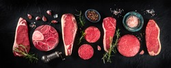 Various cuts of meat, shot from above on a dark background with condiments, a flat lay panorama