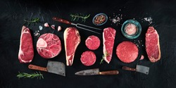 Various cuts of meat, shot from the top on a black background with condiments and knives, a flat lay panorama