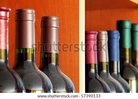 various dark red wine bottles row on shelf
