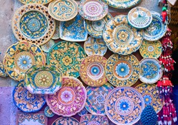 Various decorated pottery dishes hung for sale outside a souvenir shop in Erice, Sicily