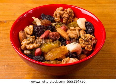 various different mixed nuts and raisins on wooden background