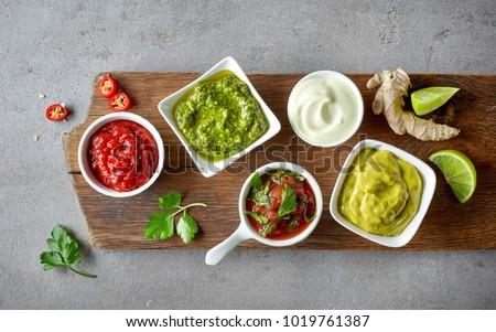 various dip sauces on grey table, top view