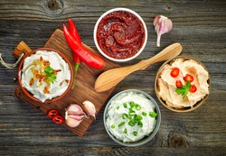 various dip sauces on wooden table, top view