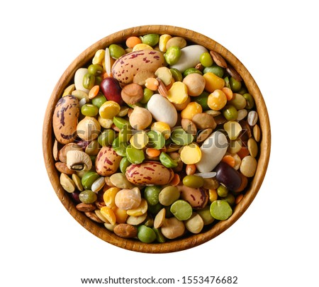 Various dried legumes: lentils bean pea chickpea in a wooden cup top view isolated on white.