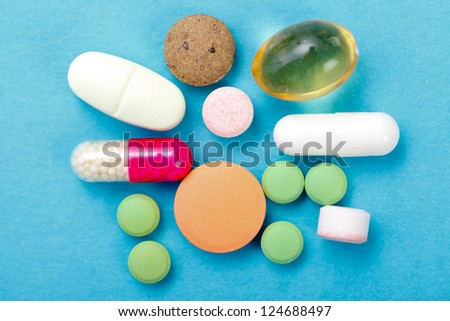 Various drugs, nutrient supplements and vitamins on blue background.