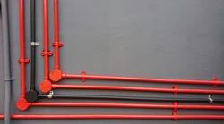 Various electrical metal conduits in red, black and gray are installed on a gray wall of building. Circular electric angle box cable conduit fittings are made at each turning points.