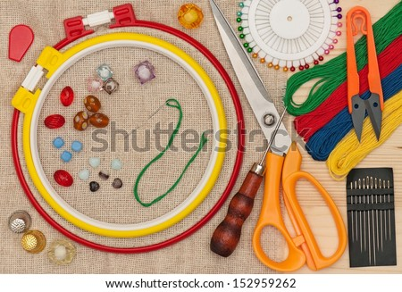 Various embroidery accessories with buttons and beads over outline