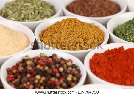 Various exotic spices in white bowls. Selective focus on the curry powder.