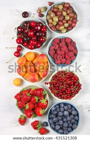 Various fresh fruits in bowls in rows on white wooden background: strawberries, blueberries, raspberries, cherries, red currants, gooseberries and apricots. Top view point.
