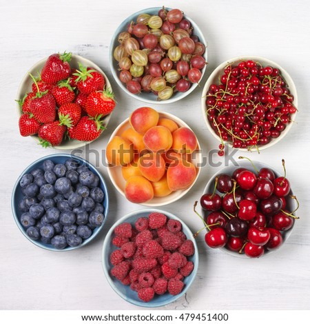 Various fresh fruits in bowls on white wooden background: strawberries, blueberries, raspberries, cherries, red currants, gooseberries and apricots. Top view.