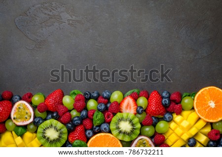 Various fresh fruits: strawberry, raspberry, blueberry, tangerine, grape, mango, spinach on a dark black stone background. Copy space, top view, horizontal image