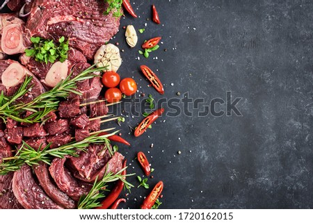 Various fresh meat-portioned steaks, beef tenderloin, shin steaks, meat on skewers lie on a dark background. The meat is decorated with seasonings, vegetables and herbs. Top view, free space for text.