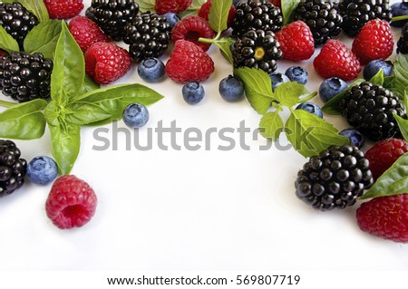 Various fresh summer berries on a white background. Ripe blueberries, raspberries and blackberries. Berries at border of image with copy space for text. Background berries. Top view  #569807719