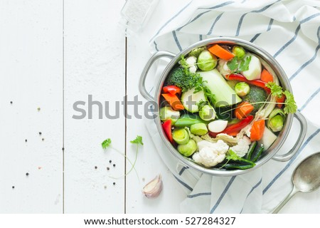 Various fresh vegetables in a pot - colorful fresh clear spring soup (vegetarian bouillon or stock). Rural kitchen scenery from above (top view). White wooden background - layout with free text space. #527284327