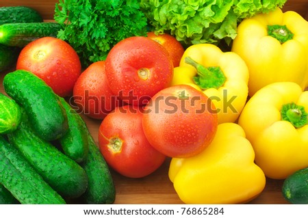 Various fresh vegetables in wooden tray.