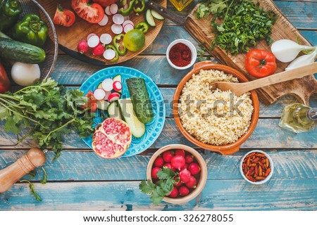 Various fresh vegetables on a blue wooden table  and cook burghul in ceramic bowl ready to prepare arabian traditional food. Country food concept from above. Series.