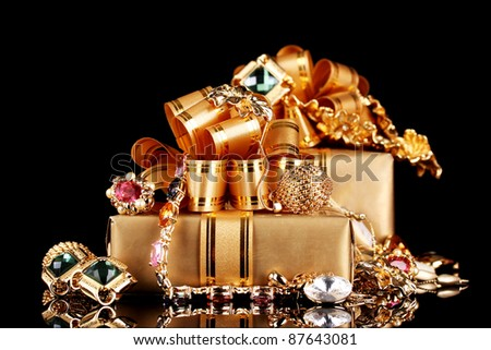 Various gold jewellery and gifts on black background