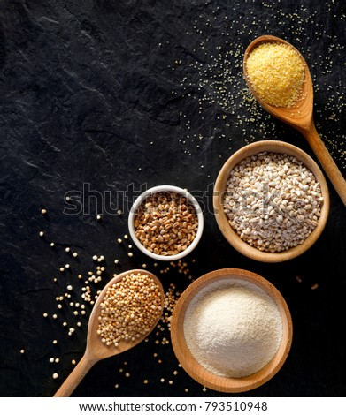 Various groats, cereals. Different types of groats in bowls and on a spoons on a  black background, top view. Healthy nutrition food Stockfoto ©