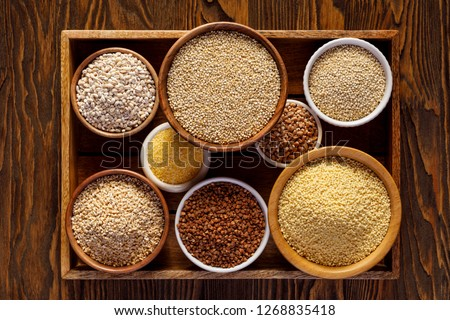 Various groats, cereals. Different types of groats in bowls on a wooden background, top view. Healthy nutrition food, healthy eating concept Stockfoto ©