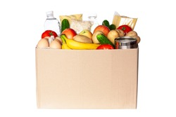 Various grocery items in cardboard box isolated on white background. Food box with fresh vegetables, fruits, cereals, pasta, milk, eggs and canned goods. Food delivery or donation concept.