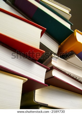 Various hardcover books stacked next to each other