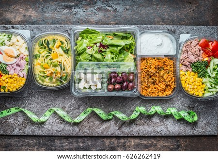 Various Healthy lunch boxes in  plastic package and green measuring tape on rustic background, top view. Dieting food concept.