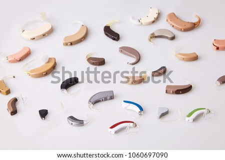 Various hearing aids on white background, alternative to surgery. ENT accessory